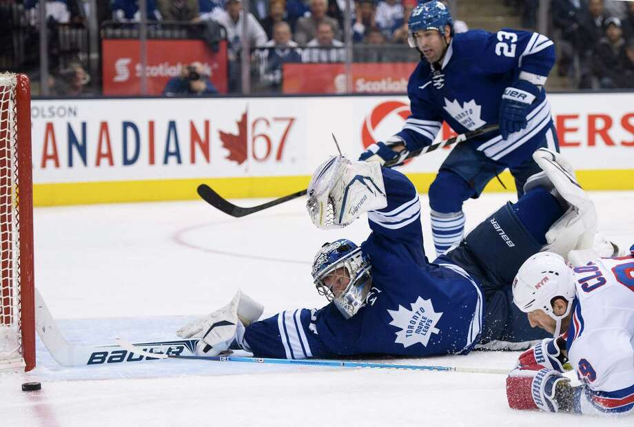 Toronto Maple Leafs goalie James Reimer, center, makes a diving save on a shot by New York Rangers forward Ryane Clowe, right, as Maple leafs defenseman Ryan O'Byrne, rear, watches during the third period of their NHL hockey game in Toronto, Monday, April 8, 2013. (AP Photo/The Canadian Press, Nathan Denette) Photo: Nathan Denette