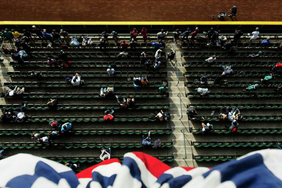Fans sitting in the outfield enjoy the last rays of sunlight during player warm up. Photo: JORDAN STEAD / SEATTLEPI.COM