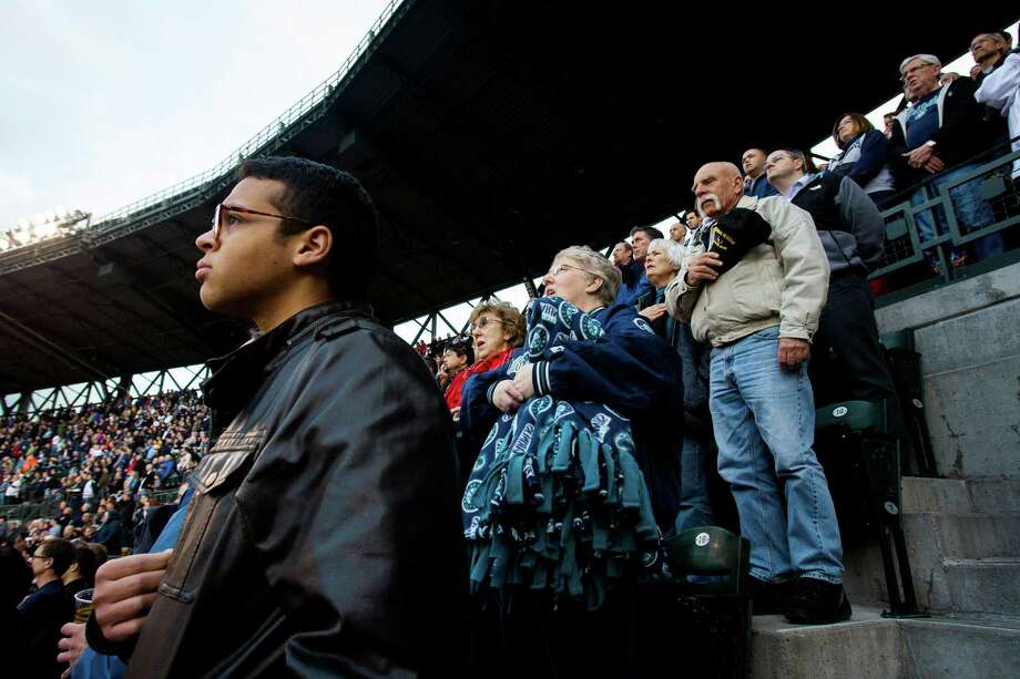 Sam Nelson, left, backed by a full house in the 300 section, listens to the national anthem before the Seattle Mariners opening home game against the Houston Astros. Photo: JORDAN STEAD / SEATTLEPI.COM