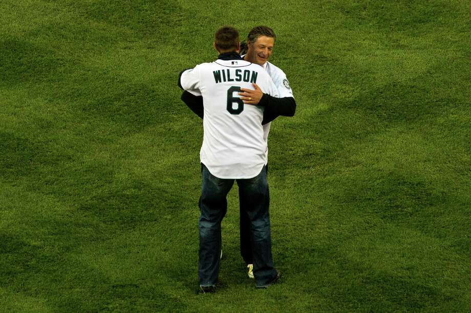 After throwing out the first pitch, Jamie Moyer, background, embraces Dan Wilson, foreground, before the Seattle Mariners opening home game against the Houston Astros. Photo: JORDAN STEAD / SEATTLEPI.COM