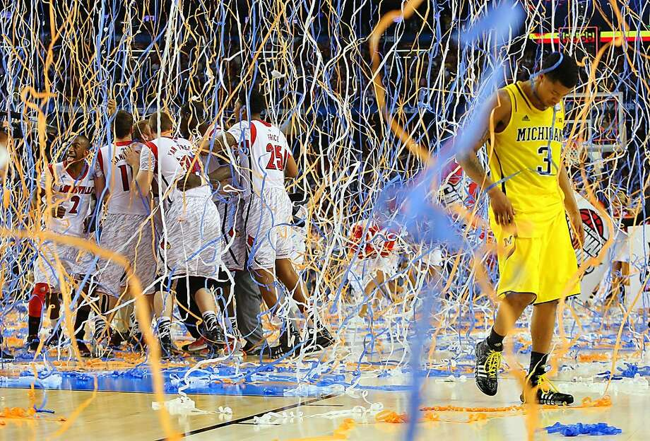 Head down,Michigan guard Trey Burke walks off the court as confetti rains on jubilant Louisville players following the Cardinals' 82-78 victory in the NCAA Tournament championship game. Photo: Curtis Compton, Associated Press
