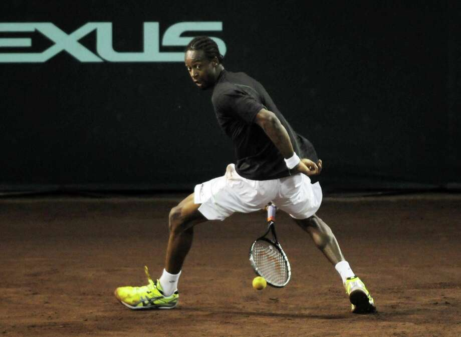 Gael Monfils displays his acrobatic skills as he tries to return a shot to James Blake during Monfils' 7-6 (5), 7-5 win in the first round Monday night. Photo: Bob Straus / (c)Bob Straus