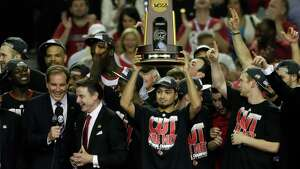 Louisville guard Peyton Siva (3) holds the winning trophy with his team mates after Louisville defeated Michigan after the second half of the NCAA Final Four tournament college basketball championship game Tuesday, April 9, 2013, in Atlanta. Louisville won 82-76. (AP Photo/Chris O'Meara)