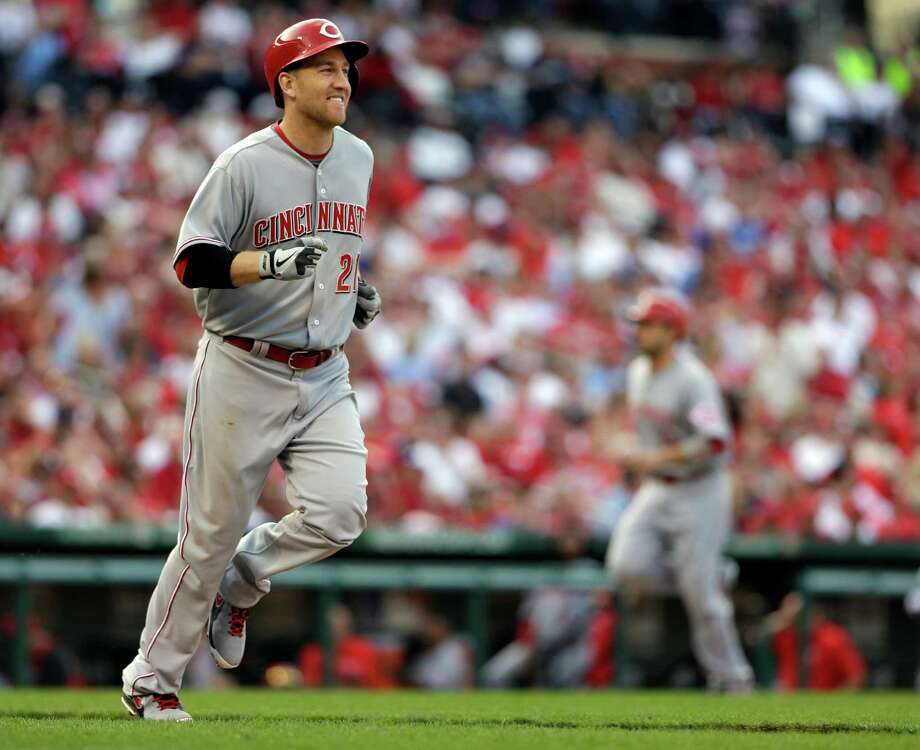 Cincinnati Reds' Todd Frazier, left, walks with the bases loaded to score Joey Votto, rear right, during the ninth inning of a baseball game against the St. Louis Cardinals, Monday, April 8, 2013, in St. Louis. The Reds won 13-4. (AP Photo/Jeff Roberson) Photo: Jeff Roberson