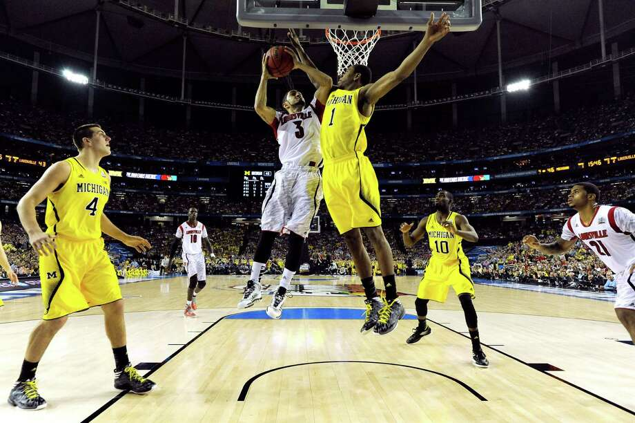 ATLANTA, GA - APRIL 08:  Peyton Siva #3 of the Louisville Cardinals drives for a shot attempt against Glenn Robinson III #1 of the Michigan Wolverines during the 2013 NCAA Men's Final Four Championship at the Georgia Dome on April 8, 2013 in Atlanta, Georgia.  (Photo by Chris Steppig-Pool/Getty Images) Photo: Pool / 2013 Getty Images