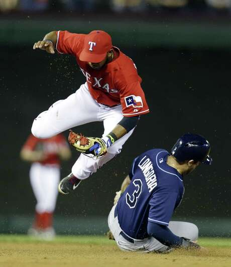 Rangers shortstop Elvis Andrus jumps out of the way as the Rays' Evan Longoria breaks up a double play attempt. Photo: LM Otero / Associated Press