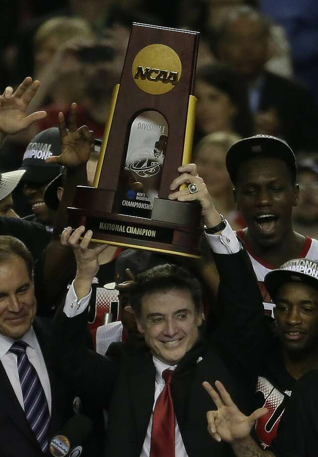 Rick Pitino and his Louisville players raise the championship trophy after he became the first coach to win national championships at two schools. Photo: Chris O'Meara, Associated Press