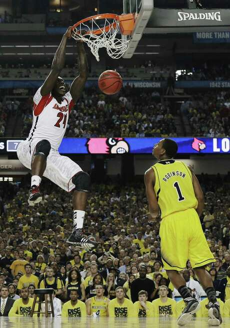 Louisville forward Montrezl Harrell dunks emphatically for his only two points of the game off a lob from Peyton Siva as Michigan forward Glenn Robinson III watches helplessly. The basket capped a 16-3 Louisville first-half run. Photo: Charlie Neibergall / Associated Press