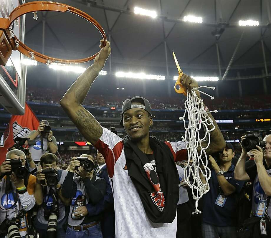 Louisville guard Kevin Ware holds the net after Louisville defeated Michigan 82-76 after the second half of the NCAA Final Four tournament college basketball championship game Tuesday, April 9, 2013, in Atlanta. (AP Photo/David J. Phillip) Photo: David J. Phillip, Associated Press