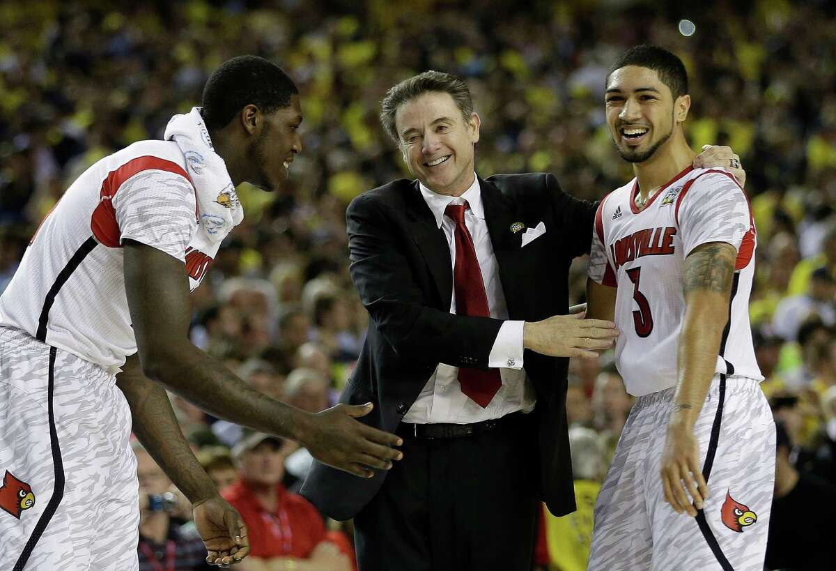 Louisville coach Rick Pitino and guard Peyton Siva begin to celebrate the victory that makes Pitino the first coach to win national titles at two schools.