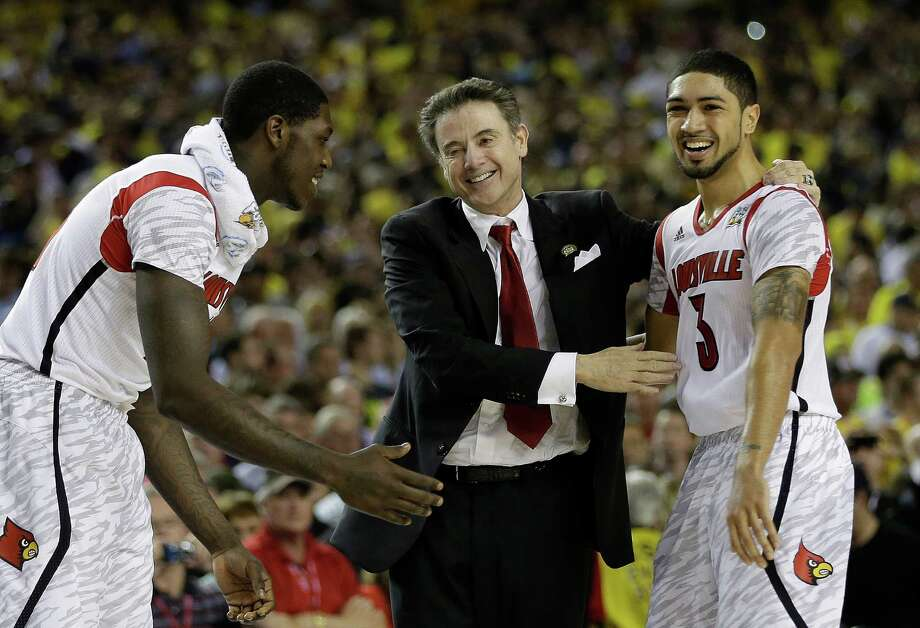 Louisville coach Rick Pitino and guard Peyton Siva begin to celebrate the victory that makes Pitino the first coach to win national titles at two schools. Photo: David J. Phillip, STF / AP