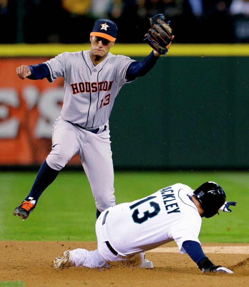 Astros shortstop Ronny Cedeno begins to jump out of the way as Dustin Ackley slide safely into second base. Photo: Elaine Thompson, Associated Press