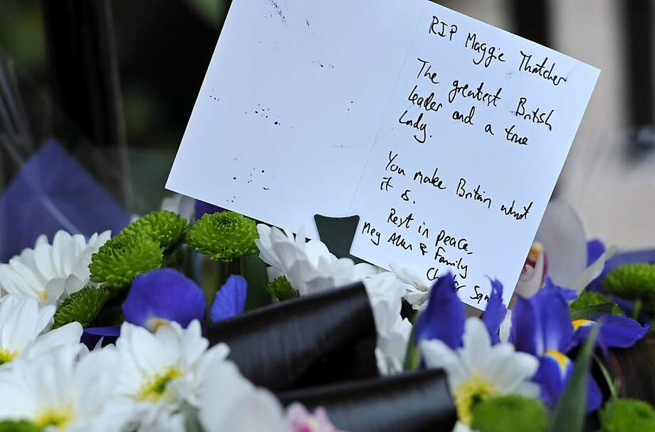 """TOPSHOTS A written tribute and flowers are pictured outside the home of former British Prime Minister Margaret Thatcher in central London, on April 08, 2013, following her death earlier Monday. Margaret Thatcher, the """"Iron Lady"""" who shaped a generation of British politics, died following a stroke on Monday at the age of 87, her spokesman said.  AFP PHOTO / CARL COURTCARL COURT/AFP/Getty Images Photo: Carl Court, AFP/Getty Images"""