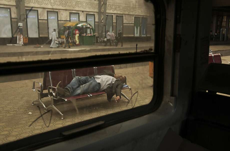 An Egyptian man lays down as he waits for hours due to a train drivers strike at the main train station in Cairo, Egypt, Monday, April 8, 2013. A union of Egypt's train drivers and conductors announced on Sunday April 7, 2013 that they have gone on strike, the latest in a seemingly endless series of work stoppages to hit the country in the past two years.The strike began, hours after authorities approved a 10 percent hike in the allowance routinely given to train drivers and conductors. The raise was rejected as too little. (AP Photo/Nariman El-Mofty) Photo: Nariman El-Mofty, Associated Press