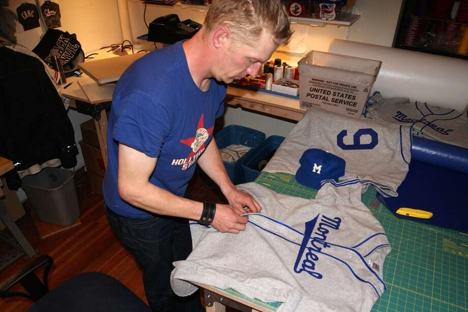 An Ebbets Field Flannels employee works on a Montreal Royals uniform for the film \'42.\'