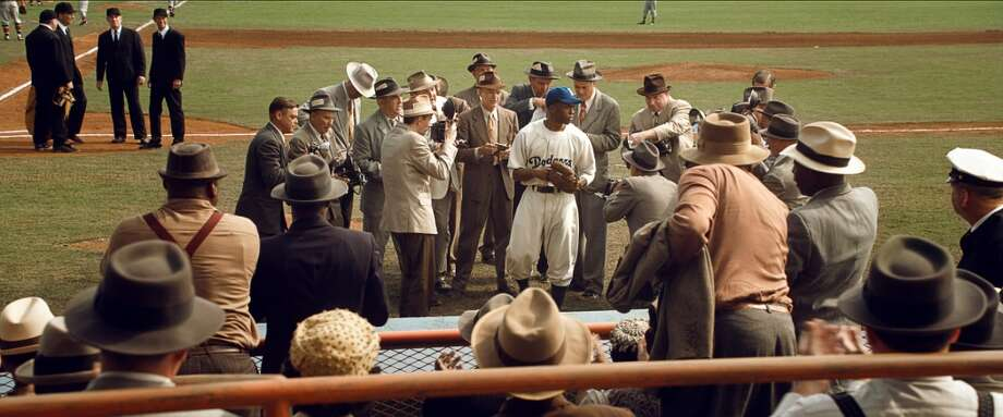 Actor Chadwick Boseman (center), as Jackie Robinson, is seen in the movie \'\'42\'\' wearing a Montreal Royals uniform produced by Seattle\'s Ebbets Field Flannels.