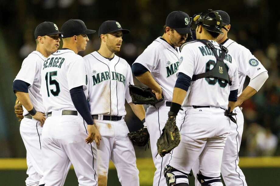 Pitcher Joe Saunders, center right, is relieved from the mound during the Seattle Mariners opening home game against the Houston Astros. Photo: JORDAN STEAD / SEATTLEPI.COM