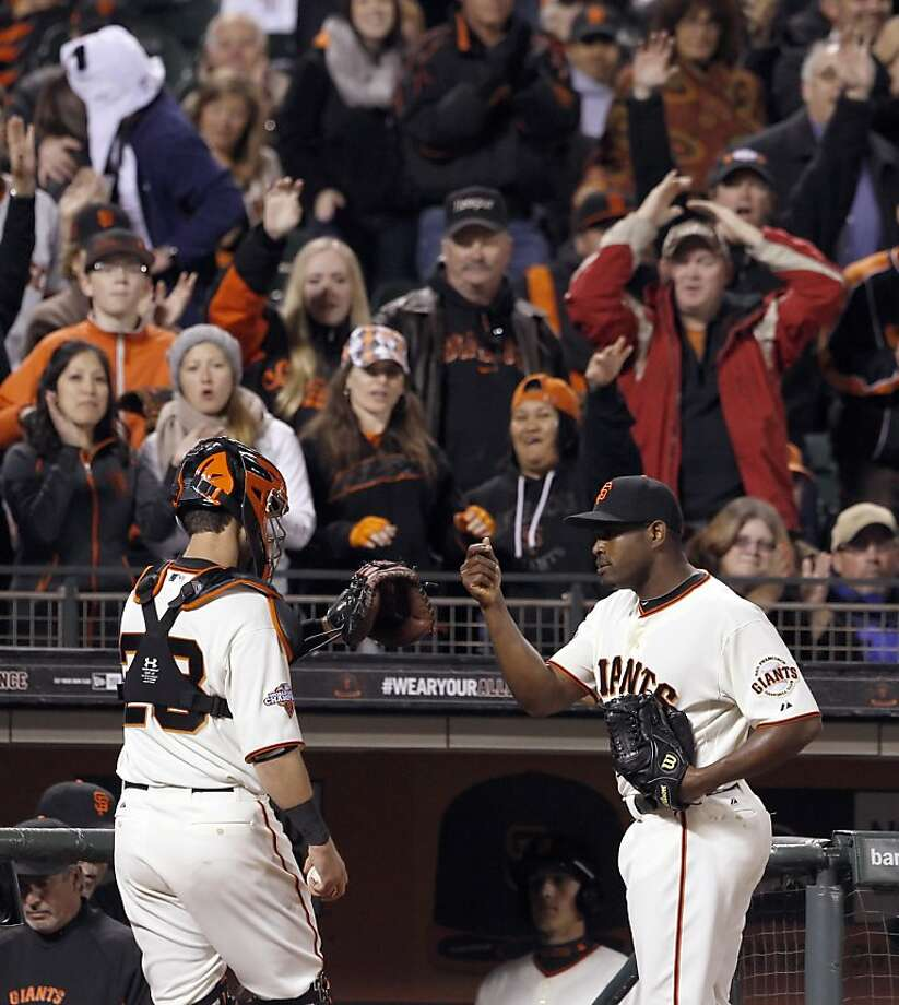 Santiago Casilla high fives Buster Posey after retiring the side in the seventh inning. The San Francisco Giants played the Colorado Rockies  at AT&T Park in San Francisco on Monday, April 8, 2013, and won 4-2. Photo: Carlos Avila Gonzalez, The Chronicle