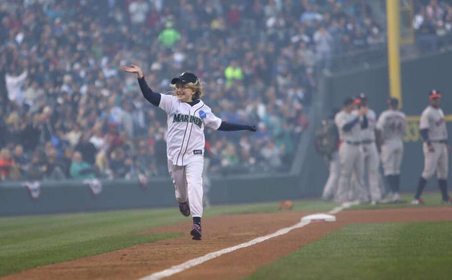 Marlee Burkett waves to cheering fans as she runs the bases during the Mariners home opener. Photo: JOSHUA TRUJILLO / SEATTLEPI.COM