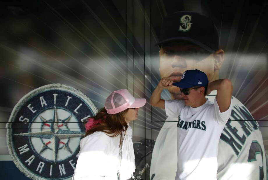 Annemarie Van Reeven and Sander Van Lingen of Holland try on their new Mariners baseball caps. Photo: JOSHUA TRUJILLO / SEATTLEPI.COM