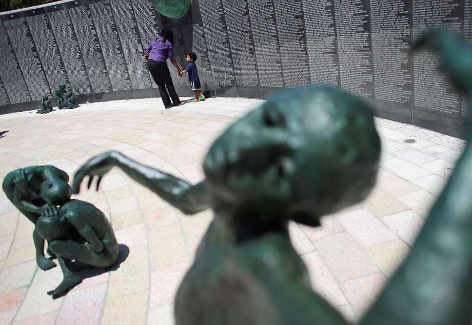 MIAMI BEACH, FL - APRIL 08: Erica Thompson (L) and three-year-old George Thompson walk past a wall of the names of some of the Holocaust victims as they visit the Holocaust Memorial during Yom HaShoah-Holocaust Remembrance Day on April 8, 2013 in Miami Beach, Florida. Holocaust Remembrance Day is observed as a day of commemoration for the approximately six million Jews who died during the Holocaust.  (Photo by Joe Raedle/Getty Images) Photo: Joe Raedle, Getty Images