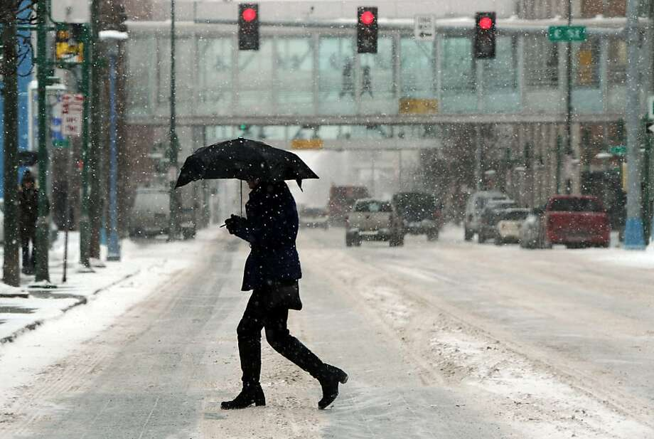 A pedestrian crosses Sixth Avenue as another spring snowstorm hits downtown Anchorage, Alaska, Monday afternoon April 8, 2013. (AP Photo/The Anchorage Daily News, Erik Hill) Photo: Erik Hill, Associated Press