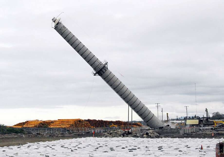 The smokestack of the former Peninsula Plywood mill in Port Angeles, Wash., falls to the ground on Monday, April 8, 2013. The 175-foot stack proved to be stronger than expected and failed to fall with explosives as planned, prompting demolition crews to cut pieces of reinforcing steel by hand and then pulling the structure down by a cable attached to an excavator. The stack fell to the ground almost three hours behind schedule. (AP Photo/Peninsula Daily News, Keith Thorpe) Photo: Keith Thorpe, Associated Press