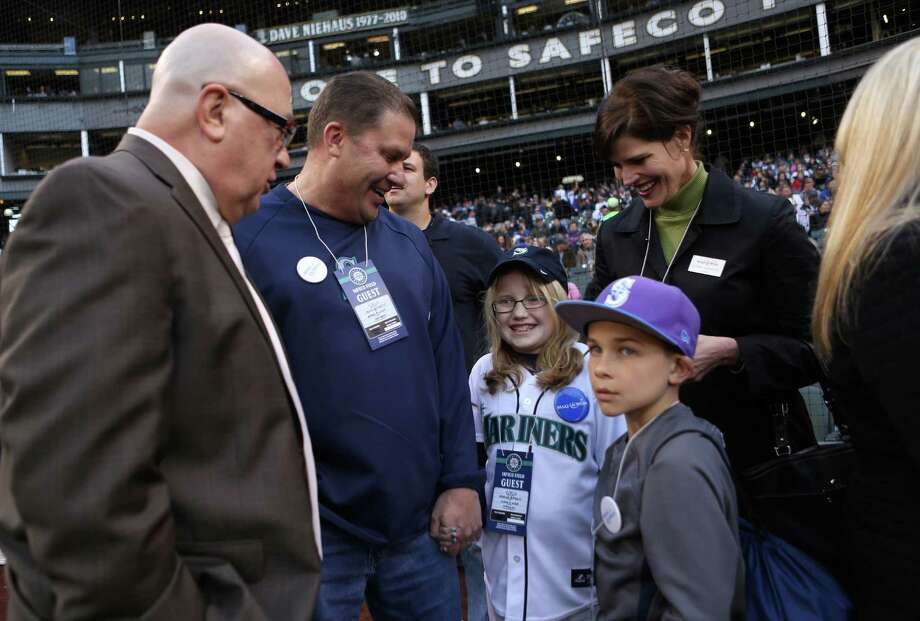 Marlee Burkett, center, tries to calm her nerves before the running the bases with help from her family and Mariners General Manager Jack Zduriencik. Photo: JOSHUA TRUJILLO / SEATTLEPI.COM