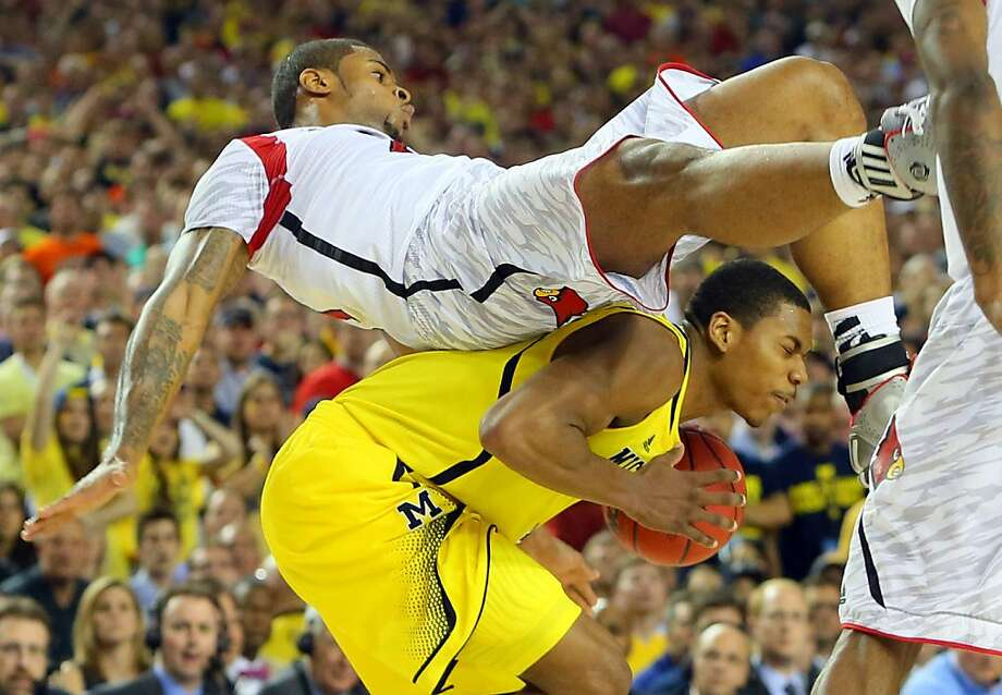 Louisville forward Chane Behanan comes down on top of Michigan forward Glenn Robinson III for a foul in the final minutes of the game. Louisville defeated Michigan 82-76 to win the NCAA Division I National Championship on Monday, April 8, 2013, in Atlanta.  (AP Photo/Atlanta Journal Constitution, Curtis Compton) Photo: Curtis Compton, Associated Press