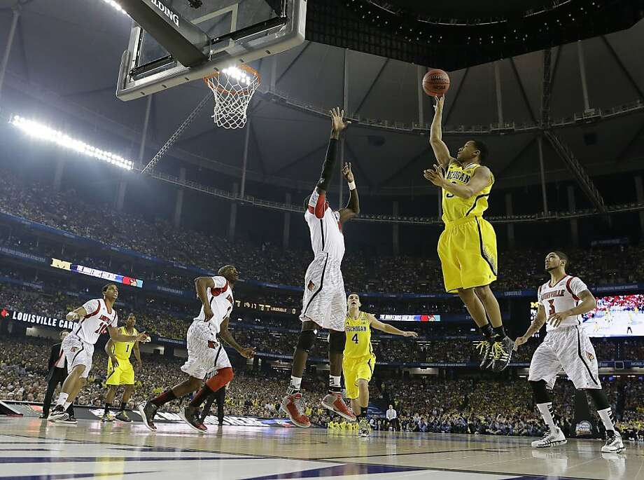 Michigan guard Trey Burke (3) shoots against a Louisville defense during the first half of the NCAA Final Four tournament college basketball championship game Monday, April 8, 2013, in Atlanta. (AP Photo/David J. Phillip) Photo: David J. Phillip, Associated Press