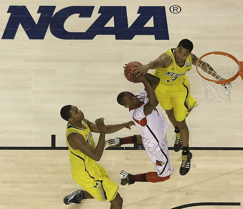 Louisville guard Peyton Siva (3) shoots under pressure from Michigan guard Trey Burke (3) and Michigan forward Glenn Robinson III (1) during the first half of the NCAA Final Four tournament college basketball championship game Monday, April 8, 2013, in Atlanta. (AP Photo/David J. Phillip) Photo: David J. Phillip, Associated Press