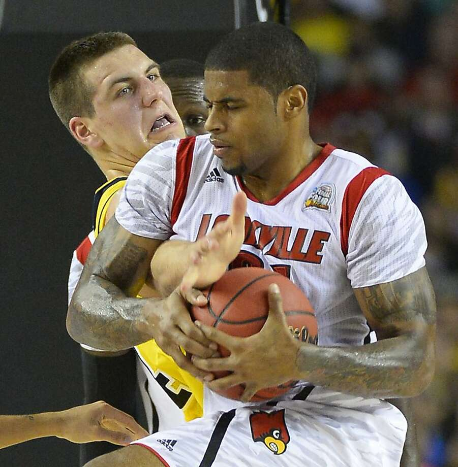 Chane Behanan (21) of the Louisville Cardinals and Mitch McGary (4) of the Michigan Wolverines battle for the ball in the first half of the NCAA Tournament final at the Georgia Dome in Atlanta, Georgia, Monday, April 8, 2013. (Harry E. Walker/MCT) Photo: Harry E. Walker, McClatchy-Tribune News Service