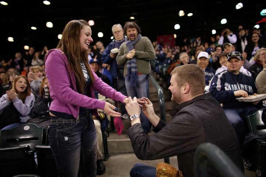 Matt Berzins places a ring on the finger of his girlfriend HaleyMae Howells. Photo: JOSHUA TRUJILLO / SEATTLEPI.COM
