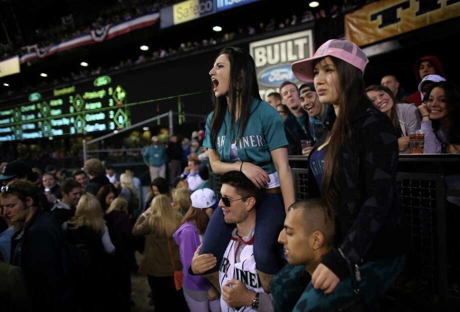 Joy Hall, left, sits on the shoulders of Scott Badgley and Stephanie Westfall sits on the shoulders of Jaiveer Nijjar for a better view during opening day. Photo: JOSHUA TRUJILLO / SEATTLEPI.COM