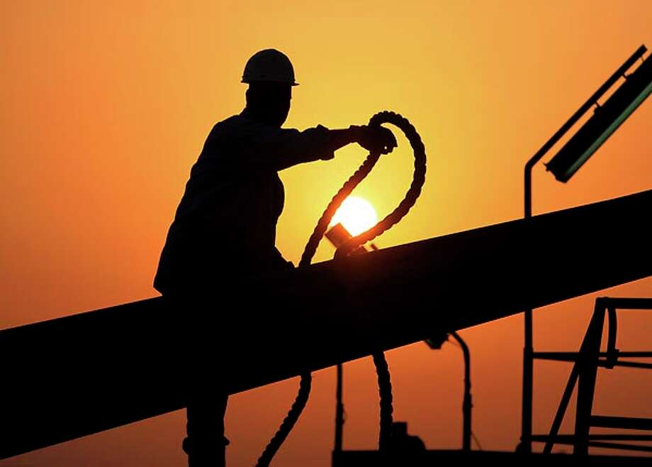 FILE - In this file photo taken July 7, 2010, an unidentified oilfield worker ties pipes to be raised on an oil rig as the sun sets in the Persian Gulf desert oil field of Sakhir, Bahrain. Exxon earned the majority of its income from exploration and production operations in foreign waters, particularly in Africa, Asia and the Middle East. Exxon's results showed a jump in profits across its exploration and production, refining and chemicals businesses. Photo: Hasan Jamali, AP / AP