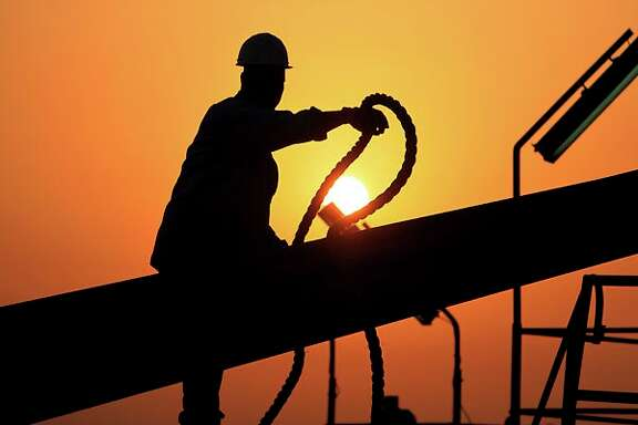 FILE - In this file photo taken July 7, 2010, an unidentified oilfield worker ties pipes to be raised on an oil rig as the sun sets in the Persian Gulf desert oil field of Sakhir, Bahrain. Exxon earned the majority of its income from exploration and production operations in foreign waters, particularly in Africa, Asia and the Middle East. Exxon's results showed a jump in profits across its exploration and production, refining and chemicals businesses.