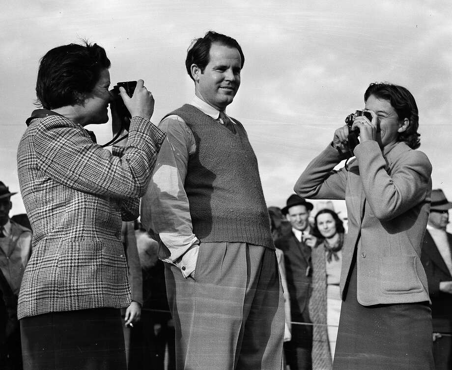 "Ralph Guldahl of Madison, N.J., center, National Open Champion who April 2, 1939 broke the tournament record with a 72 hole score of 279 to win the sixth annual Augusta National Golf Tournament at Augusta, Ga. Guldahl is shown posing for a couple of golf playing candid camera fans after completing the final round. The ""cameramen"" are Katherine Hemphill, left, of Columbia, S.C. and Dorothy Kirby of Altanta, Ga. Photo: Associated Press / AP"