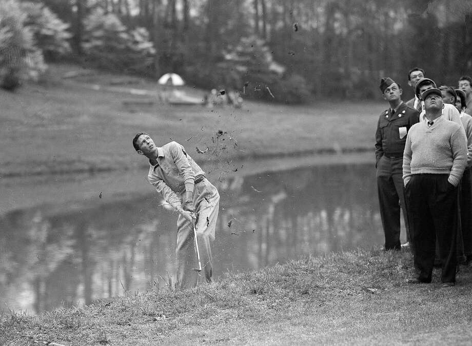 Golfer Charlie Coe makes a splash as he drives his ball from the mud at the edge of a lake bordering the 15th green, during second round of the Masters Golf Tournament at Augusta, Ga., April 6, 1951. Photo: Horace Cort, Associated Press / 2008 AP