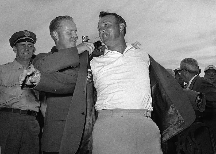 Arnold Palmer, right, slips into his green jacket with help from Jack Nicklaus after winning his fourth Masters golf championship on April 12, 1964. Photo: Associated Press / AP1964