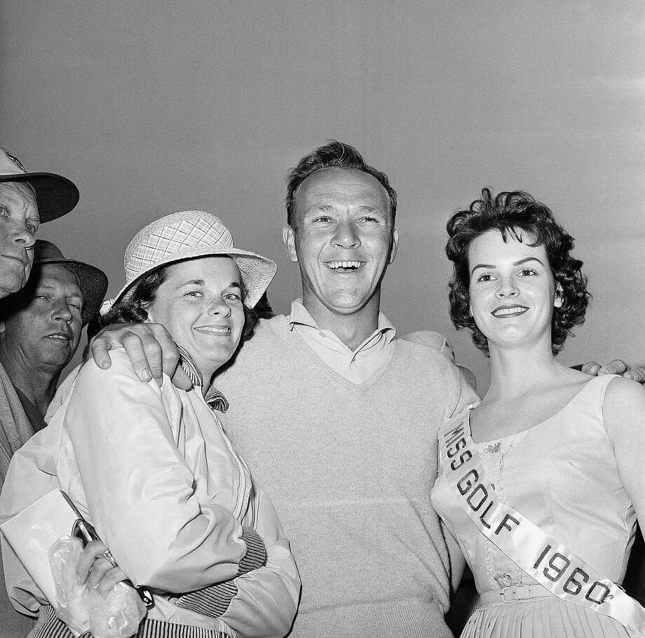 Arnold Palmer, center, smiles happily with his wife Winnie, left, and Miss Golf, Glenda Gunter, Langley, S.C., after April 9, 1960 Masters Golf action in Augusta, Ga.. Palmer held the lead with a 212. Photo: Horace Cort, Associated Press / AP1960