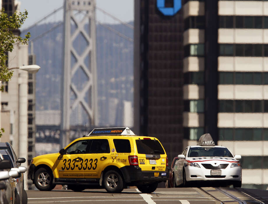 Two taxis cross paths on California Street and Mason Street in San Francisco, Calif., on Monday, April 8, 2013. A report for the SFMTA by a taxi consultant says the city needs 600-800 more taxis. Photo: Carlos Avila Gonzalez, The Chronicle / ONLINE_YES