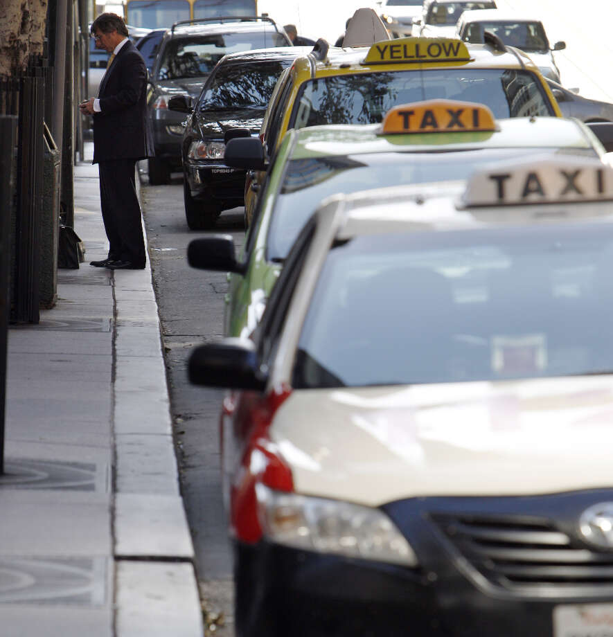 A man walks by a line of taxis waiting in a taxi zone at 555 California Street in San Francisco, Calif., on Monday, April 8, 2013. A report for the SFMTA by a taxi consultant says the city needs 600-800 more taxis. Photo: Carlos Avila Gonzalez, The Chronicle / ONLINE_YES