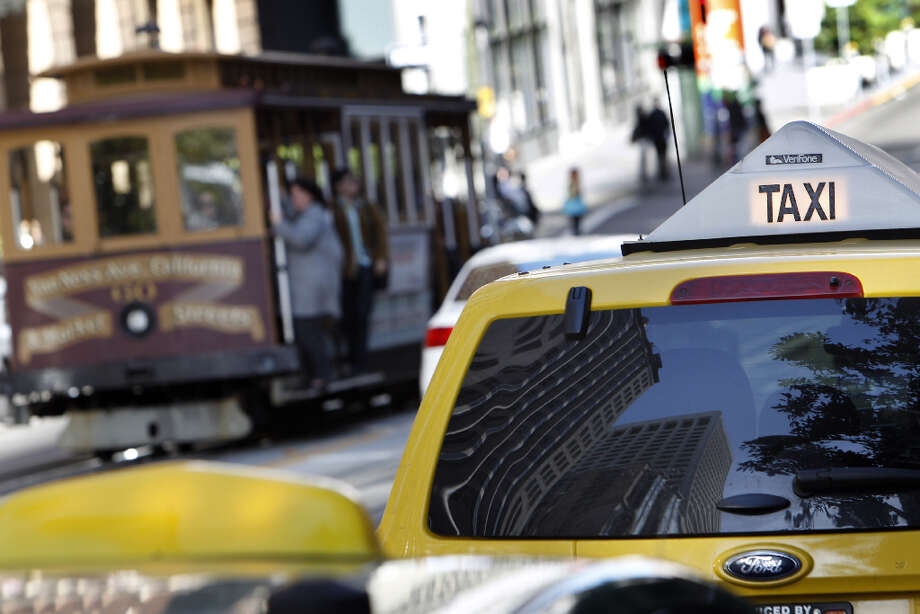 A cable car passes a taxi passes a taxi at a stand on California Street in San Francisco, Calif., on Monday, April 8, 2013. A report for the SFMTA by a taxi consultant says the city needs 600-800 more taxis. Photo: Carlos Avila Gonzalez, The Chronicle / ONLINE_YES
