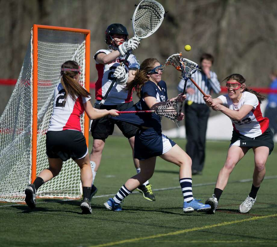 Wilton's Sara Dickinson takes a shot as she is surrounded by New Canaan's Lizzy Burke, left, goalie Liz O'Sullivan, center, and Olivia Hompe, right, during Saturday's girl's lacrosse game at New Canaan High School on April 6, 2013. Photo: Lindsay Perry / Stamford Advocate