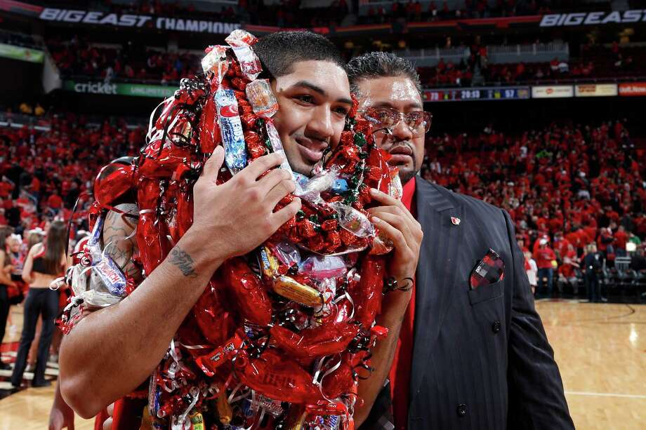 Peyton Siva #3 of the Louisville Cardinals leaves the floor with his father adorned with candy around his neck after the game against the Notre Dame Fighting Irish at KFC Yum! Center on March 9, 2013 in Louisville, Ky. Louisville defeated Notre Dame 73-57. Photo: Joe Robbins, Getty Images / 2013 Joe Robbins