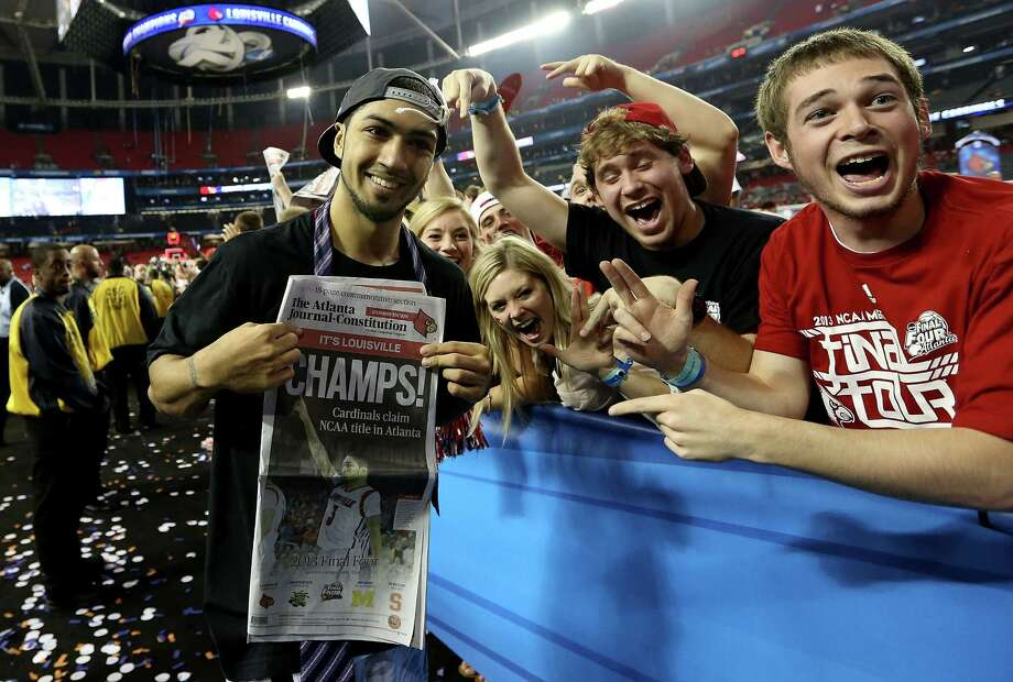 "Peyton Siva #3 of the Louisville Cardinals holds up a newspaper which reads ""Champs"" as he celebrates with fans after Louisville won 82-76 against the Michigan Wolverines during the 2013 NCAA Men's Final Four Championship at the Georgia Dome on April 8, 2013 in Atlanta, Ga. Photo: Streeter Lecka, Getty Images / 2013 Getty Images"