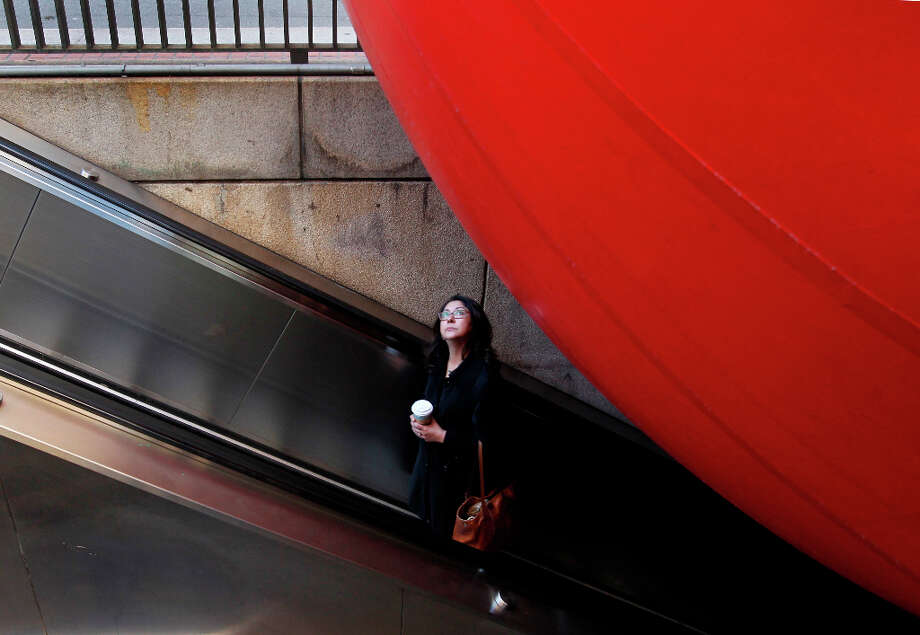 A woman stares at a giant inflatable ball perched overhead as she leaves the Embarcadero BART station in San Francisco, Calif. on Tuesday, April 9, 2013. Artist Kurt Perschke brought his Red Ball Project art installation to the station for the day to entertain and amuse commuters as they arrived and departed. Photo: Paul Chinn, The Chronicle / ONLINE_YES