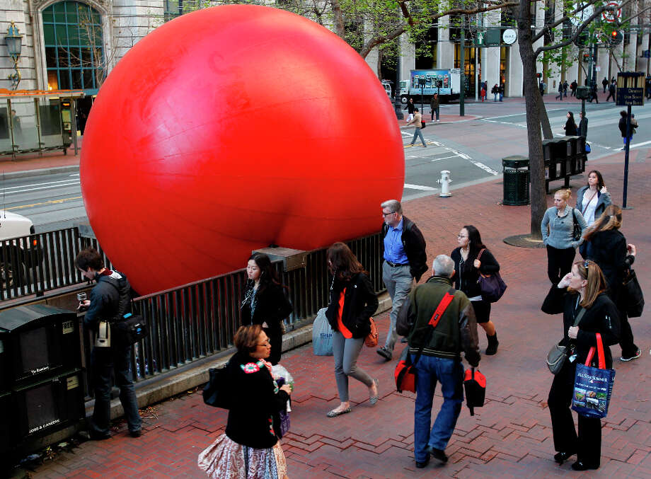 Pedestrians walk past a giant inflatable ball at the Embarcadero BART station in San Francisco, Calif. on Tuesday, April 9, 2013. Artist Kurt Perschke brought his Red Ball Project art installation to the station for the day to entertain and amuse commuters as they arrived and departed. Photo: Paul Chinn, The Chronicle / ONLINE_YES