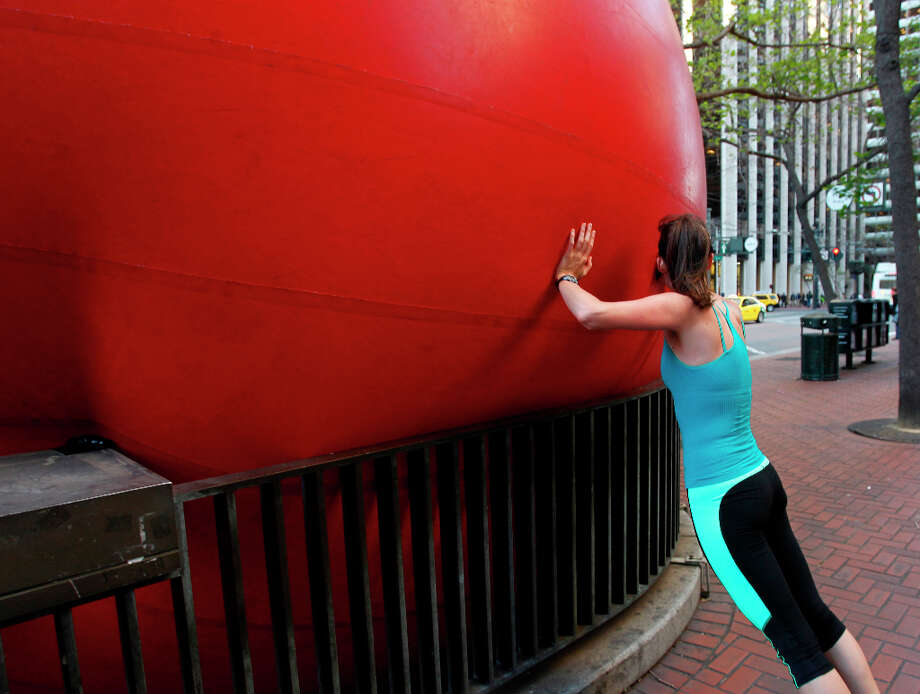 Laura Weyl tries to nudge a 15-foot inflatable ball at the Embarcadero BART station in San Francisco, Calif. on Tuesday, April 9, 2013. Artist Kurt Perschke brought his Red Ball Project art installation to the station for the day to entertain and amuse commuters as they arrived and departed. Photo: Paul Chinn, The Chronicle / ONLINE_YES