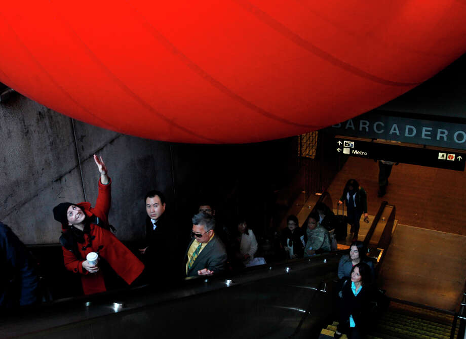 Isabel Archer reaches out to touch a 15-foot inflatable ball wedged into a stairway at the Embarcadero BART station in San Francisco, Calif. on Tuesday, April 9, 2013. Artist Kurt Perschke brought his Red Ball Project art installation to the station for the day to entertain and amuse commuters as they arrived and departed. Photo: Paul Chinn, The Chronicle / ONLINE_YES